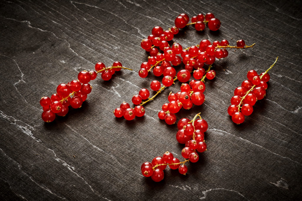 delicious and juicy red currant on an old black wooden table