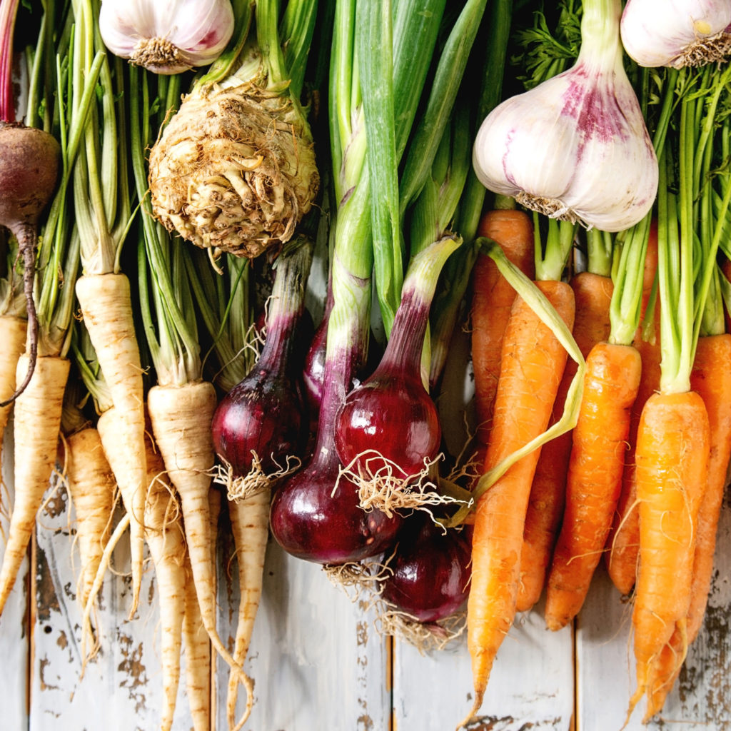 Variety of root garden vegetables carrot, garlic, purple onion, beetroot, parsnip and celery with tops over white wooden background. Flat lay, space